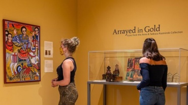 Two people viewing Arrayed in Gold exhibit
