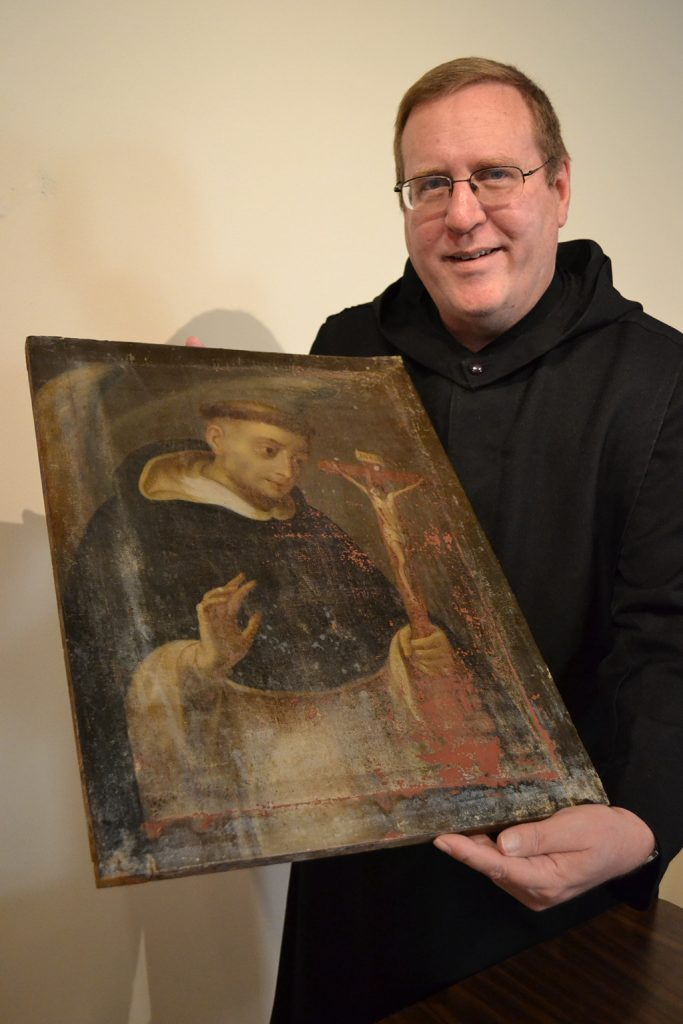 Nathan Cochran O.S.B. holding painting of Saint Dominic